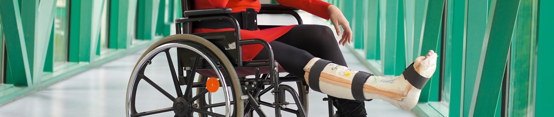 Vrouw zit in rolstoel met gebroken been